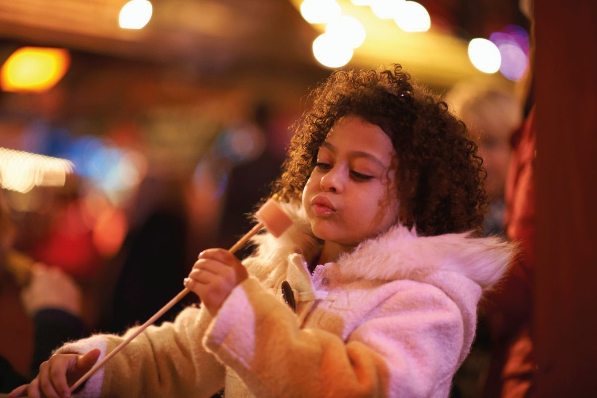 Young girl at funfair, blowing on toasted marshmellow